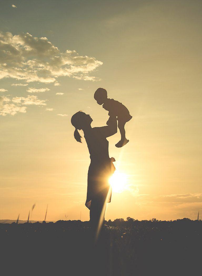 Femme avec enfant - coucher du soleil